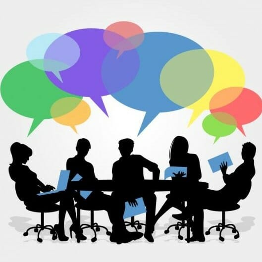 Speech bubbles floating above people engaged in a meeting