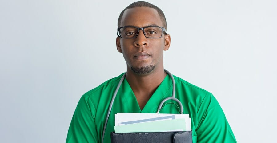 Close-up of serious young African American doctor with folder