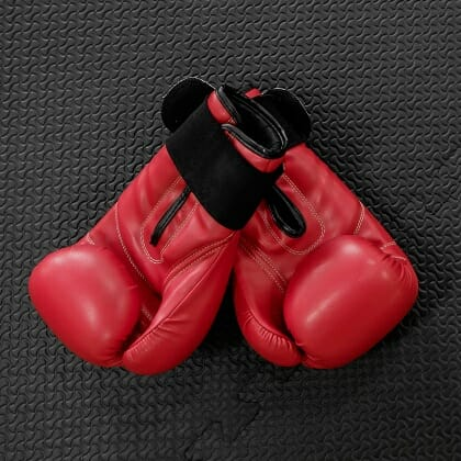 boxing gloves hang on nail on texture wall with copy space for t