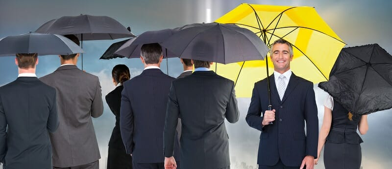 Older male with a yellow umbrella standing out in a crowd