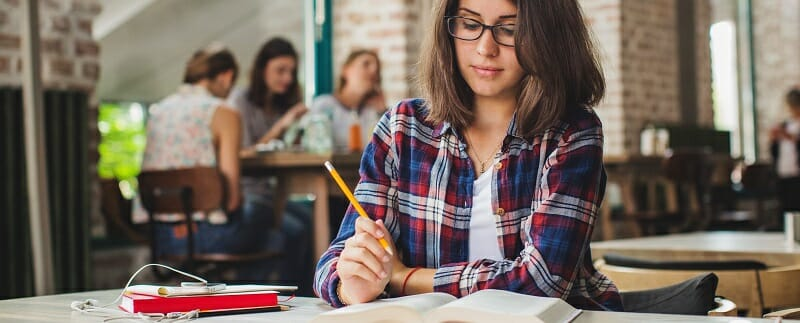 Young woman sitting alone studying with pencil in hand