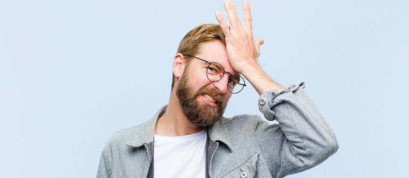 Young blonde man raising palm to forehead thinking oops, after making a stupid mistake or remembering, feeling dumb