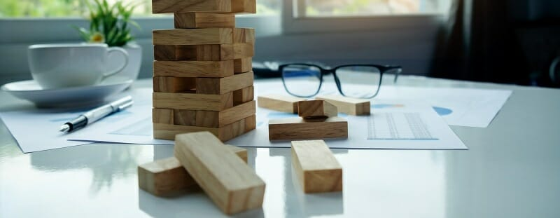 Desk with wooden blocks among loose business documents