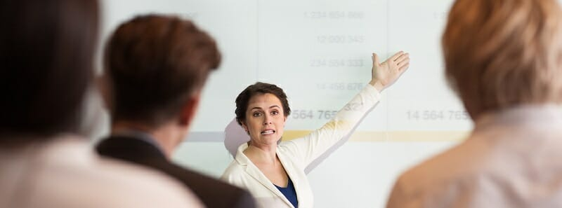 Serious Businesswoman Showing Table to Audience