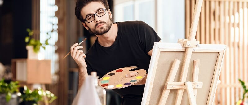 an painting with brush standing behind easel